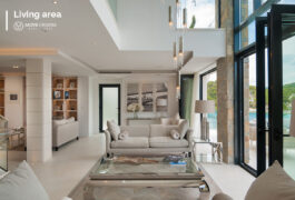 A modern glass cofee table and a white sofa in the middle of the living room.