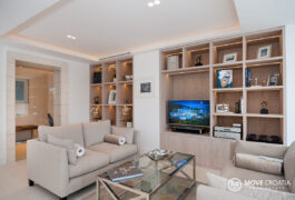 Multiple modernly designed shelfs with books and a smart tv in the living room.