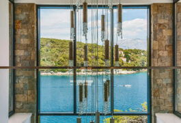 The luxury chandelier in front of a large window which looks directly on the sea.