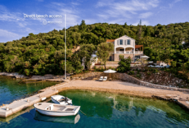 White Mediterranean seaside villa with a boat mooring, hidden with green pine trees.