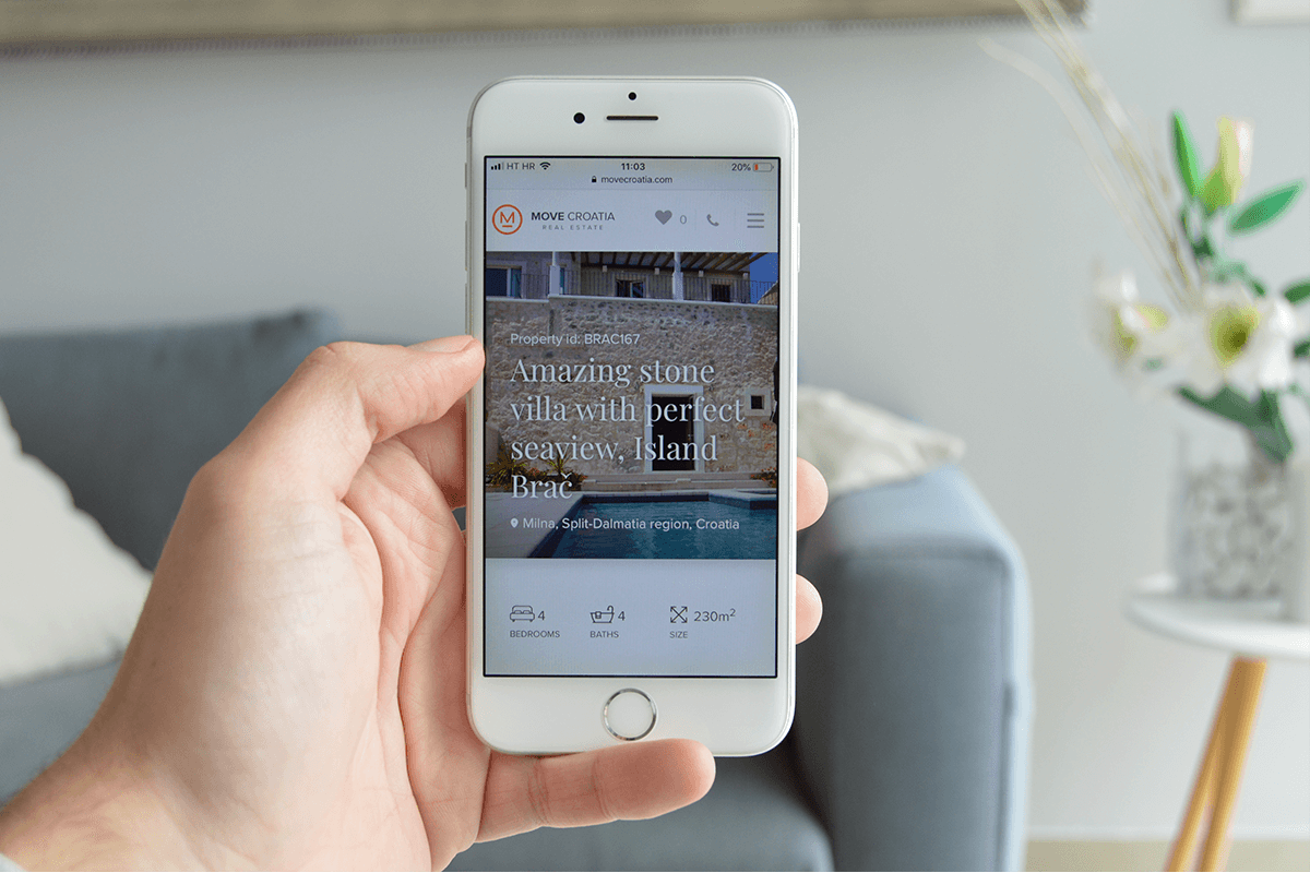 White smartphone that shows a property on a real estate website.