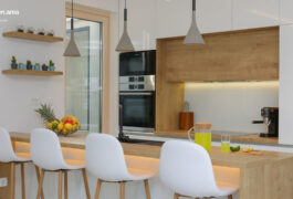 A modern kitchen area with a wooden bar, white furniture, and modern electrical appliances.