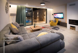 A living room inside of mansion with big grey couch and a yellow chair, tv and a fireplace.