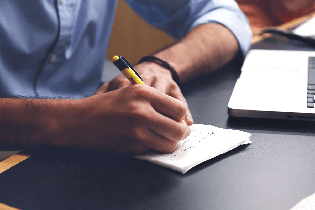 A man with a blue shirt writing notes on a white paper.