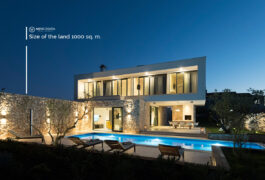 Night shot of a lit white modern villa built in stone, with a swimming pool.