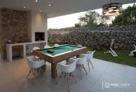 A pool table surrounded with 7 modern white chairs and a barbecue in the background.