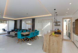 The kitchen, dining table, and living room situated on the same large floor.