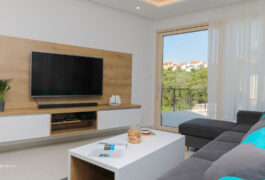 Modern living area with a large tv in the middle of the wall, and a large window with a view.