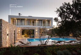 Modern mansion built in stone with a pool and three sunbeds.